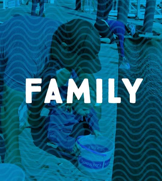 Family returning a sturgeon to Lake Michigan
